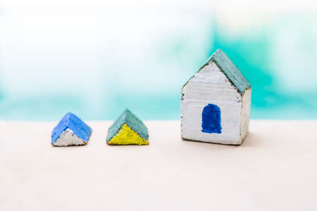 Handmade wooden house model for small garden decoration over blurred background, simple design miniature house