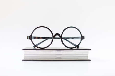 Eyeglasses on thick book isolate on white background, fashion reading eyeglasses with black frame Stok Fotoğraf