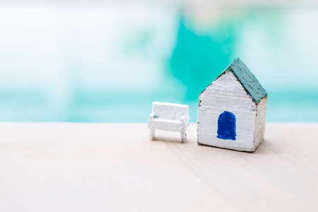 Small wooden house model with white chair over blurred blue water background, outdoor day light, house and property or insurance and house loan concept
