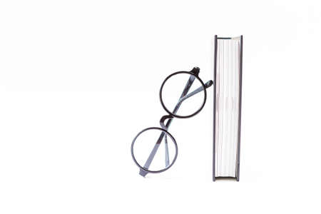Eyeglasses with thick book isolate on white background, education concept, design fashion reading glasses