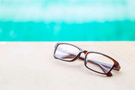 Eyeglasses on swimming pool edge with space on blurred blue water background, outdoor day light, design women reading glasses, relax by the pool