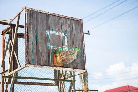 Old basketball ring on an old wooden shield with shabby paint over clear blue sky, outdoor day light, sport concept Stok Fotoğraf