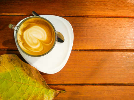 Hot coffee latte on wooden table background with fresh leaf on the side, coffee break time, latte art Stok Fotoğraf