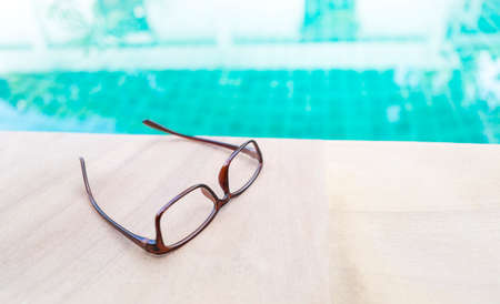 Reading glasses on swimming pool edge, women glasses design, relaxing by the pool Stok Fotoğraf