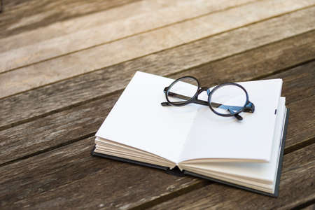 Reading glasses on blank notebook on wooden floor, outdoor day light, education concept Stok Fotoğraf