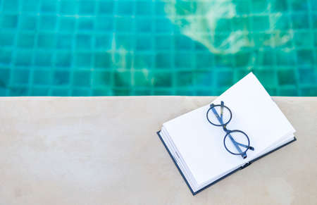 Eyeglasses on blank notebook on swimming pool edge with space on blurred blue water background, outdoor day light, relaxing by the pool