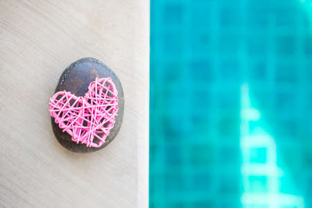 Pink wooden heart and stone on swimming pool edge with space on blurred blue water background, love and romance symbol, valentine concept background