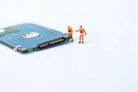 Miniature worker with hard disk on white background, computer service and maintenance business concept