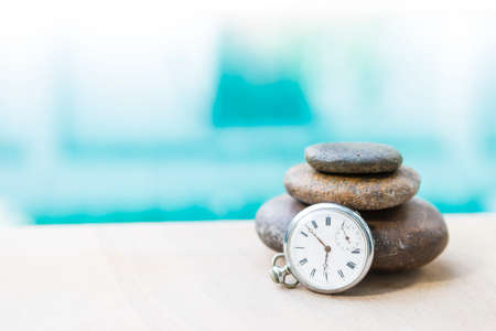 Vintage watch with zen stone over blurred blue water background, outdoor day light, peaceful time