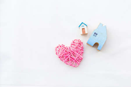 Miniature house and pink wooden heart on white background, vintage tone style, house insurance and loan business concept, new hosue Stok Fotoğraf