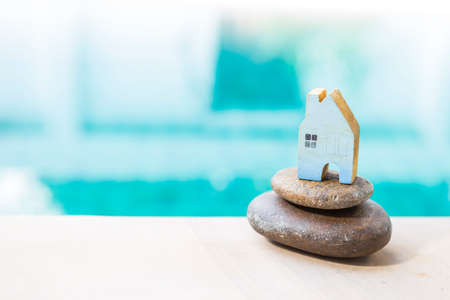Blue wooden house model on stack of stone over blurred blue water background, property business concept, new house