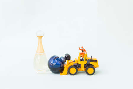 Front end loading truck clearing perfume bottles, clearance sale, miniature worker on yellow truck moving bottle on white background Stok Fotoğraf