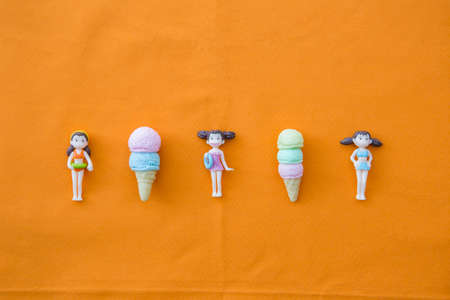 Miniature girl doll in swimming suit with icecreams on orange background, summer concept background