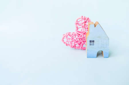 Blue wooden house model with pink wooden heart on white background, property and loan business Stok Fotoğraf