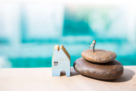 Miniature couple on stack of stone with wooden blue house over blurred background, new house celebration, property business