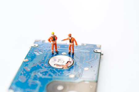Miniature worker in safty suit on hard disk drive on white background, computer specialist, computer repair and maintenance, service and spare part Stok Fotoğraf