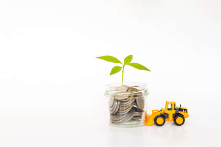 Coins in glass cup with young green plant and yellow truck on white background, truck pushing project to grow, growing business, banking industrial and financial idea