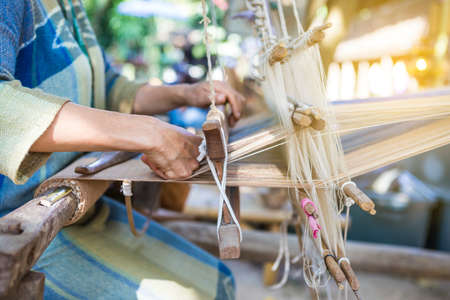 Closeup Thai girl with wooden loom, Thai style weaving, outdoor day light, textile industry Standard-Bild