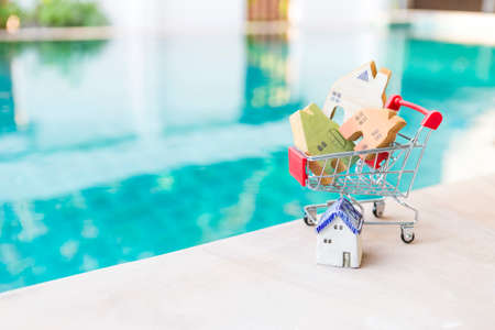 Miniature vintage style wooden house model in shopping cart over blurred swimming pool background, summer sale, property business, outdoor day light