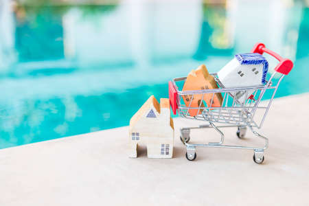 Wooden house model in shopping cart over blurred swimming pool water background, outdoor day light, property and real estate business concept, buy and sell house