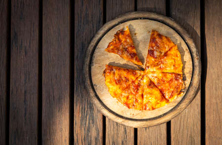 Home made margarita pizza on  round wooden cutting board on wooden floor with morning outdoor day light, easy simple homemade food Stok Fotoğraf