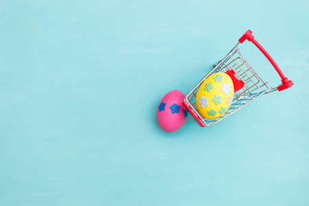 Yellow easter egg decorate with paper flower in shopping cart with space on blue texture background, happy easter card background idea Stok Fotoğraf