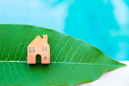 Wooden miniature orange color house on fresh green leaf over blurred blue water background, eco house concept, outdoor day light