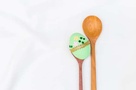 Green easter egg on wooden spoon with space on white fabric texture background