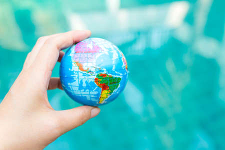 Earth day concept, plastic global ball in girl hand over blurred blue water background, outdoor day light, international earth day concept