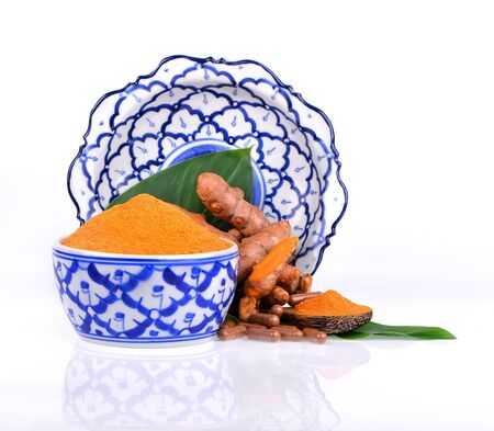 Turmeric powder in a Thai pattern ceramic cup and in a wooden spoon complete with turmeric roots and leaves.