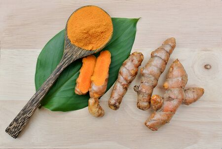 Turmeric powder in a wooden spoon on the leaves of turmeric root Stock fotó