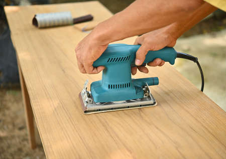 Man repairing a wooden table With hand-made machinery equipment To improve living houses ; Device blue electric energy
