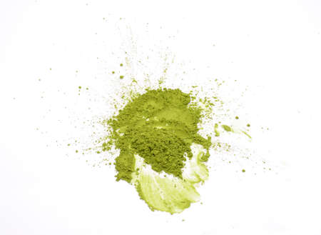 Matcha powder explosion on white background top view. Matcha is made of finely ground green tea powder. It's very common in japanese culture. Matcha is healthy due to it's high antioxydant count.