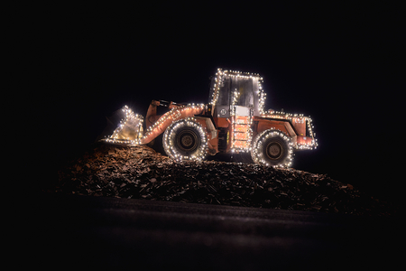 Blurred wheel loader decorated with lights bokeh