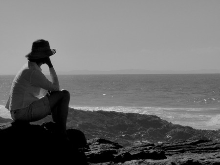 Young alone woman sitting and thoughtful looking out on sunset beach. Rear view of female missing boyfriend and family in tropical summer sea. Sad and lonely concept. Archivio Fotografico