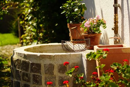 Beautiful garden with vintage water well Stock Photo - 133050255