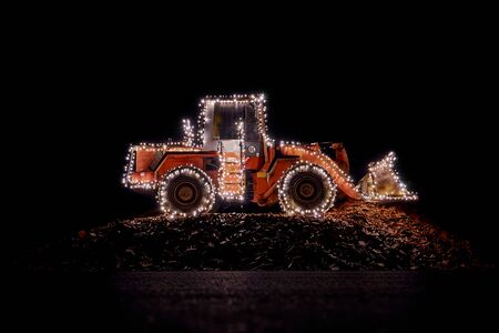 Blurred wheel loader decorated with lights in winter