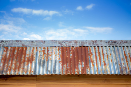 teakwood: Old iron roof on teakwood house with blue sky and white clouds