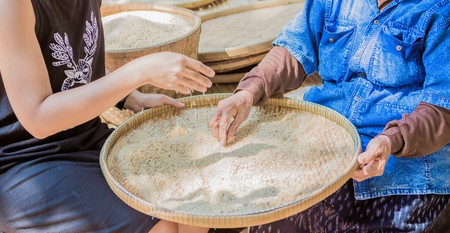 winnowing: 2 generations of woman in the lacal of Thailand are winnowing rice by using bamboo basketwork soft focus ,vintage style