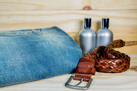 leather belt: Men Jeans And Leather Belt  on wood background with  shadows