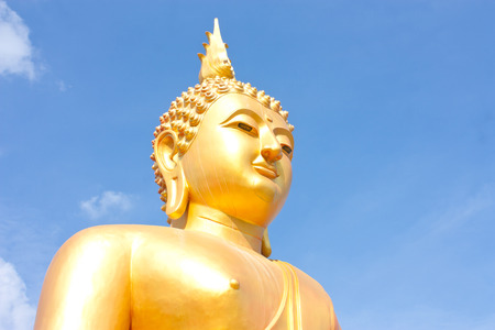 big golden Buddha statues on bluy sky background