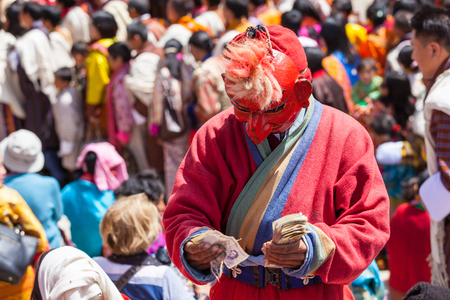 Paro,Bhutan-Apr 4,2015;Buddhist lama in traditional dress of Atsara(holy teacher) collects money offering merit from people at Rinpung Dzong during mask dance of Paro Tshechu