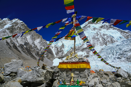 Puja site with food and drink offerings with colorful prayer flags pole for the blessing at everest base camp with himalaya mountain range in background in a clear blue sky day