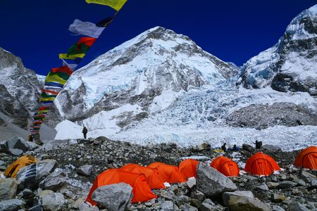 Group of climbers  bright color tents on the Khumbu glacier in area of Everest base camp with colorful prayer flags and himalaya mountain range in background during a clear blue sky day