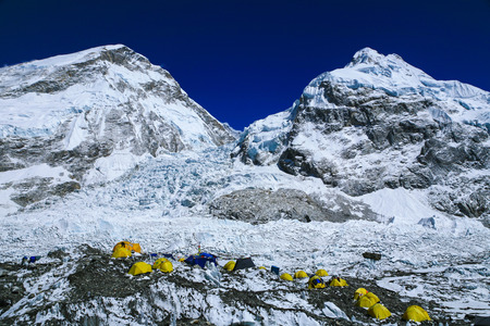 Top view for Group of climbers  bright yellow color tents on the Khumbu glacier in area of Everest base camp with himalaya mountain range in background during a clear blue sky day