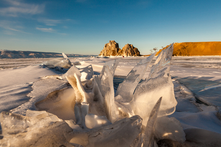 Sharp ice hummocks with holy Shama rock in background in a clear blue sky day at Olkhon island in frozen Baikal lake,Siberia,Russia