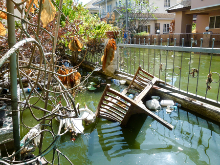 Bangkok,Thailand-Nov 27,2011;Situation after heavy flood for a month.Full of garbage,plastic bottles and wood furniture on the surface of polluted water.