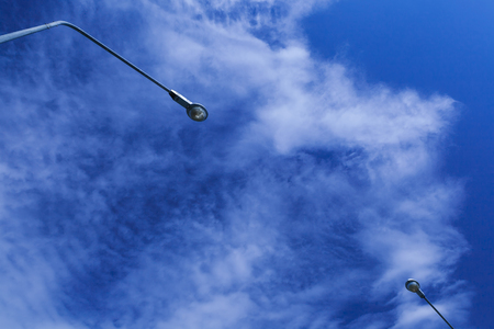 Two street electrical light lamps with the cloud and blue sky background.
