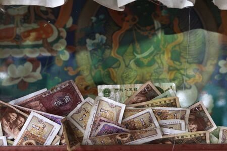 Lhasa,Tibet-May 5,2014;Money offering in front of the Buddha mural in an ancient sacred monastery to pray for the better next life and peace.