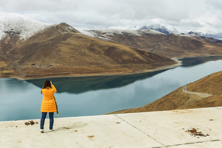 Beautiful holy Yamdrok lake with snow mountain in background and a foreign tourist shooting a picture as foreground in a cloudy day Zdjęcie Seryjne